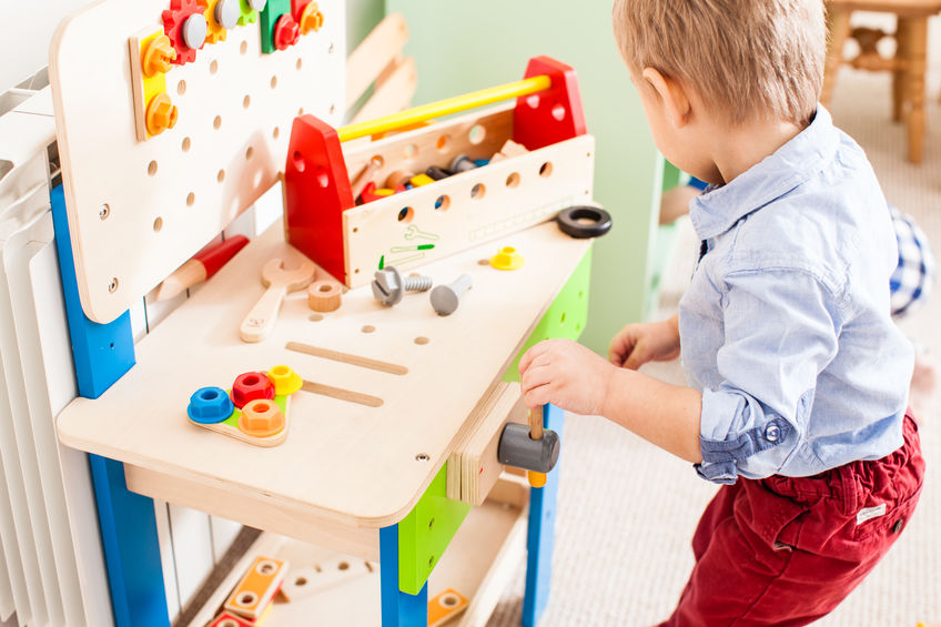 Le garçon joue avec des jouets en bois